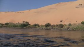 Sand dune on the bank of the river Nile in Egypt. A beautiful sand dune adjacent to the water of the River Nile in Egypt on a sunny day stock video footage