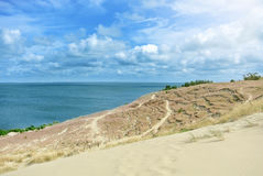 Beautiful sand dunes with a path in a dry grass and a blue Baltic sea at the background on sunny summer day Stock Image