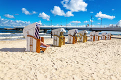 Beautiful sandy beach full of wicker chairs against blue sky Royalty Free Stock Photo