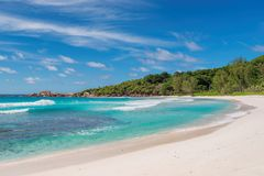 Beautiful sandy beach with palm and the turquoise sea on Paradise island. La Digue, Seychelles Royalty Free Stock Photos
