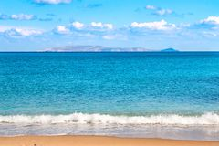 Beautiful sandy beach and soft blue sea wave on the background of the Dia island and blue sky. royalty free stock images