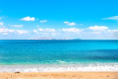 Beautiful sandy beach and soft blue sea wave on the background of the Dia island and blue sky. Copy space stock image