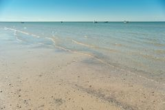 beautiful sandy beach and soft blue sea wave. panorama of seascape with blue sky at daylight. fishing boats on horizon stock photo