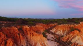 Beautiful sandy cliffs and forest at sunset Portugal Aerial view stock footage