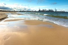 Beautiful sandy sea shore with port Stock Image