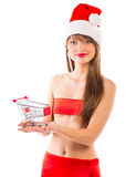 Beautiful Santa christmas girl with small shopping trolley on wh Royalty Free Stock Image