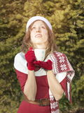 Beautiful Santa Claus girl getting warm with hot beverage Royalty Free Stock Images