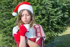 Beautiful Santa Claus girl having cup of tee outdoors stock photos