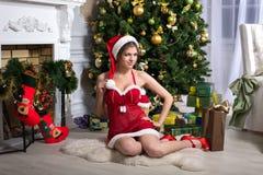 Beautiful Santa Claus helper. Beautiful girl in Santa Claus clothes sitting near the Christmas tree Stock Image