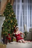 Beautiful Santa Claus helper. Beautiful girl in red party clothes sitting near the Christmas tree Stock Photo