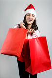 Beautiful santa girl  carrying red shopping bags. Portrait of beautiful santa girl  carrying red shopping bags Royalty Free Stock Photo