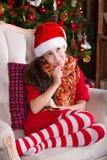 Beautiful Santa girl dreaming near the Christmas Royalty Free Stock Photography