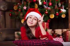 Beautiful Santa girl dreaming near the Christmas Stock Photos