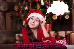 Beautiful Santa girl dreaming near the Christmas Royalty Free Stock Photo