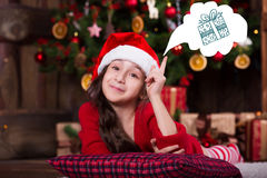 Beautiful Santa girl dreaming near the Christmas Royalty Free Stock Photos
