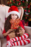 Beautiful Santa girl dreaming near the Christmas. Tree, holding a present. New year interior Stock Photo