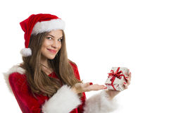 Beautiful Santa girl and gift box. Beautiful Santa girl looking at camera and holding and presenting a silver gift box over white background Royalty Free Stock Photo