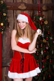 Beautiful Santa girl having fun and smiling near. The Christmas tree. New year atmosphere Royalty Free Stock Image