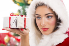 Beautiful Santa girl holding gift box. Beautiful Santa girl looking at silver Christmas gift box in her hand. Selective focus on gift box Royalty Free Stock Photo