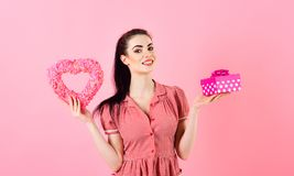 Beautiful santa girl holding heart Christmas gift Box. Over pink background , happy new year - Christmas concept royalty free stock photography