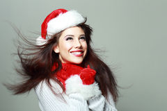 Beautiful santa girl. In red hat smiling and looking upway, windy flying hair Stock Photos
