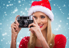 Beautiful santa woman holding camera, snowfall background Royalty Free Stock Image