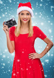 Beautiful santa woman holding camera, snowfall background Royalty Free Stock Photos