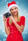 Beautiful santa woman holding camera, snowfall background Stock Photos