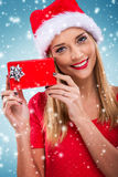 Beautiful santa woman holding gift box, blue snowfall background Royalty Free Stock Photos