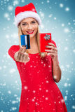 Beautiful santa woman holding gift box and credit card,snowfall background Stock Image