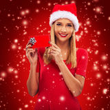 Beautiful santa woman holding gift box, red snowfall background Royalty Free Stock Images