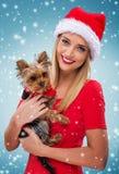 Beautiful santa woman, holding  santa yorkshite terrier, snowfall background Stock Photo