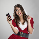 Beautiful Santa woman looking at mobile phone taking picture Stock Images