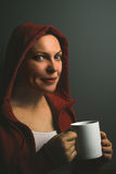 Beautiful satisfied red hooded woman drinking coffee Stock Photo