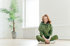 Beautiful satisfied slim woman with ginger hair, appealing appearance, sits crossed legs, wears green sweatsuit, keeps perfect. Body shape, stays fit. Athletic stock image