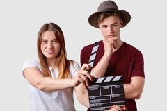 Beautiful satisfied young female holds clapperboard, signals next scene of movie, thoughtful man in hat stands in foreground,. Beautiful satisfied young female royalty free stock image