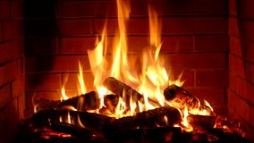 Beautiful satisfying close up shot of wood burning slowly with orange fire flame in cozy brickwork fireplace atmosphere. Beautiful satisfying close up shot of stock video footage