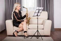 Beautiful saxophonist girl playing at her musical instrument in Royalty Free Stock Image
