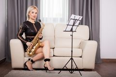 Beautiful saxophonist girl playing at her musical instrument in Royalty Free Stock Photography