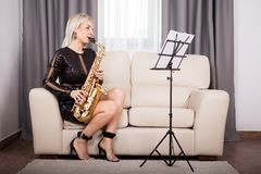 Beautiful saxophonist girl playing at her musical instrument in Royalty Free Stock Photos