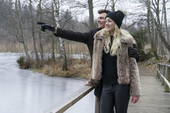 Beautiful Scandinavian young couple standing on bridge in Swedish winter landscape. Man hugging woman and pointing with hand. Royalty Free Stock Images
