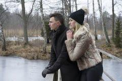 Beautiful Scandinavian young couple standing on bridge in Swedish winter landscape. Woman hugging man Stock Photo