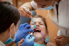 Little Girl At The Dentist. Beautiful scared little girl at visit in the dentist office. Dentist repair her teeth. Real people Royalty Free Stock Photo