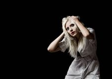 Beautiful scared young girl in the image of nurse on black background Royalty Free Stock Image