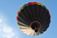Beautiful scene with a black hot air balloon. Beautiful scene with hot air balloon in the blue sky Stock Photos