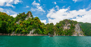 Beautiful scene of boat on green clear water with rock mountain Royalty Free Stock Image