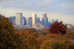 Beautiful scene of cityscape rising over tree line Stock Photos
