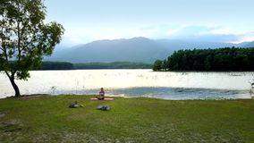Girl sits on mat meditates near tree at lake. Beautiful scene girl sits on mat meditating near large tree at tranquil lake against distant hills stock video footage