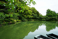 Beautiful scene of lush green japanese garden mountain landscape with shades of green plant, boats, lotus pond, etc. Royalty Free Stock Images