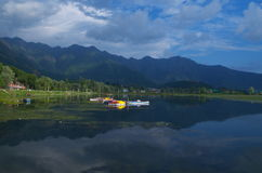 Beautiful scene near Dal lake in Kashmir-1. A beautiful scene of a blue water and dramatic sky with mountain as a backdrop in a lake in Kashmir Stock Photos
